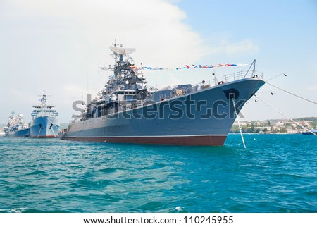 Military navy ship in the bay against blue sky