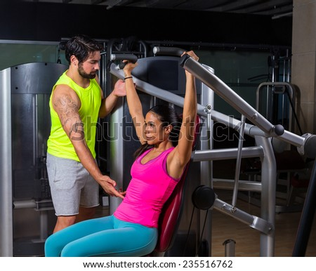 Military press machine woman with personal trainer workout at gym