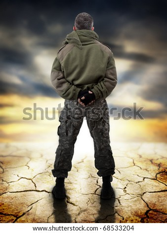 Military standing - back view, looking for apocaliptic sunrise - stock photo