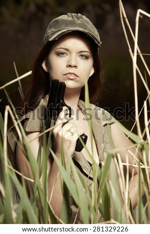 Military style beauty posing with pistol - stock photo