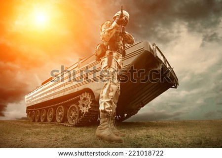 Military tank and soldier outdoors. - stock photo