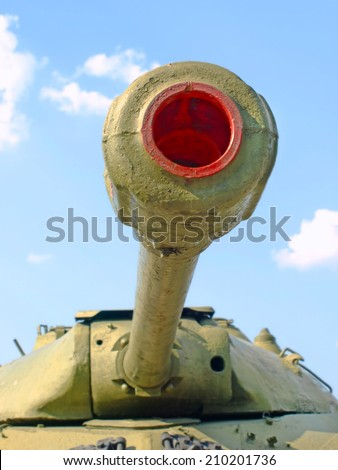 Military tank cannon against of the blue sky taken closeup. - stock photo