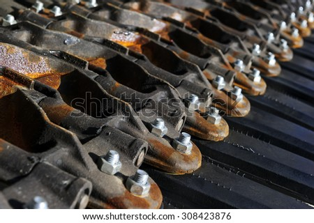 Military tank tracks with screws, bolts, black rubber parts and some rust on metal details, army industry, selective focus  - stock photo