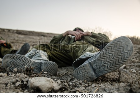 MILITARY TRAINING ZONE, ISRAEL - JUNE 4, 2013: Israeli soldiers sleeping on the ground. Exhausted soldiers after anti terror training. Combat boots close up.