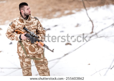 Military trooper, ranger, holding a machine gun on the battlefield - stock photo