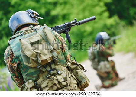 military. two soldier with assault rifle in uniform patrolling territory outdoors - stock photo