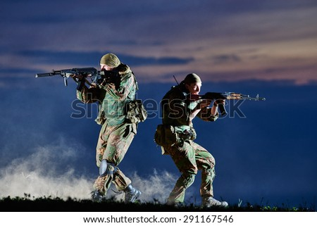 military. two soldiers in uniform running with assault rifle weapon on sunset during attack outdoors. Authentic shooting in challenging conditions. Maybe little blurred. - stock photo