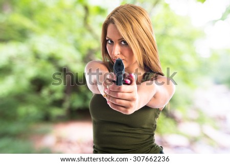 Military woman aiming a gun on unfocused background - stock photo
