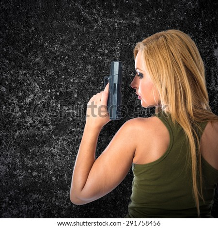 Military woman aiming a gun over textured background - stock photo
