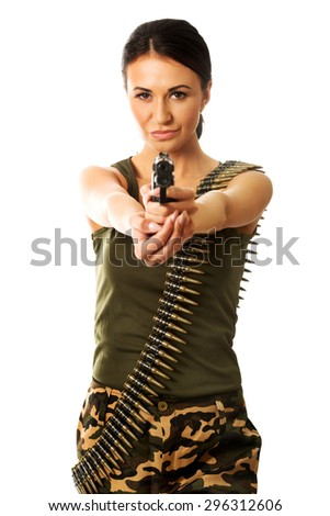Military woman wearing bullet belt and shooting by gun. - stock photo