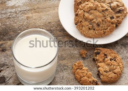 Milk and cookies in childhood tradition with a glass of farm fresh creamy milk and plate of choc chip cookies with one broken one on the old rustic wooden table - stock photo