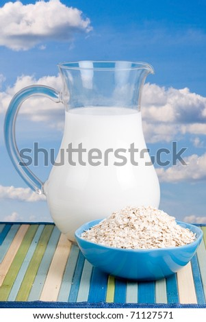 Milk  and  oatmeal  on  the background of the cloudy sky - stock photo