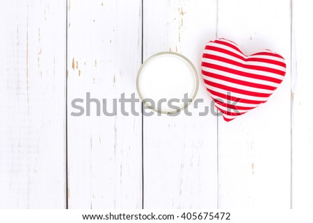 Milk and red heart on white wooden table - stock photo