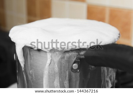 Milk boiling over a pan - stock photo