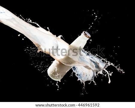 Milk bottle and splashes isolated on black background - stock photo