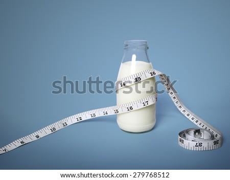 Milk bottle with Waist tape measure - stock photo