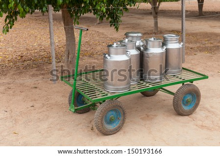 Milk cans on a cart - stock photo
