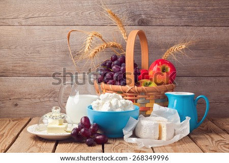 Milk, cheese and fruit basket over wooden background. Jewish holiday Shavuot celebration - stock photo