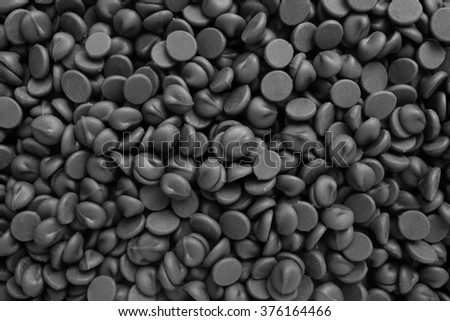 Milk chocolate chips as an abstract background texture - monochrome processing - stock photo