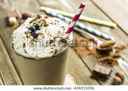 Milk chocolate drink with a straw on a background of cocoa and chocolate - stock photo