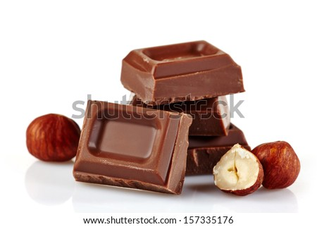 milk chocolate pieces and whole nuts on a white background - stock photo