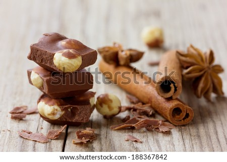 Milk chocolate slices with nuts, cinnamon sticks and anise star on a wooden rustic background, selective focus - stock photo