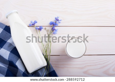Milk cup and bottle on wooden table with flower - stock photo