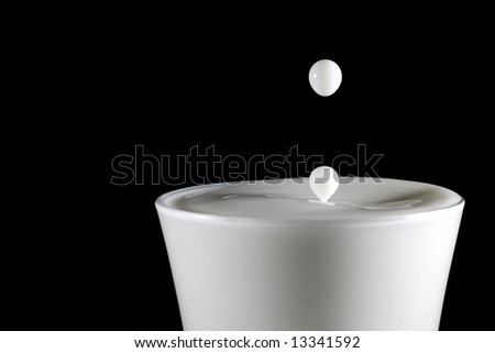 Milk drops falling into a glass of milk on a black background - stock photo