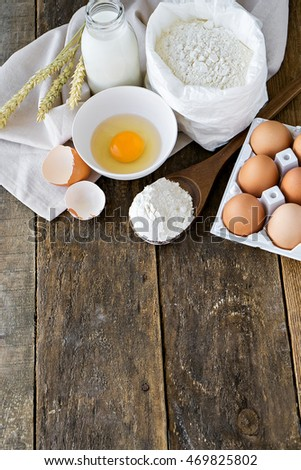 milk, eggs, flour and kitchen tools on wooden table