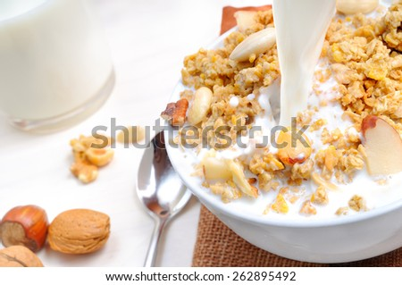 milk falling on a bowl full of cereal with dried fruits and glass of milk at the bottom - stock photo