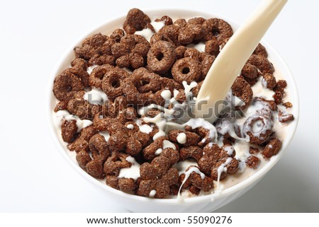 Milk flowing in a bowl with corn-flakes - stock photo
