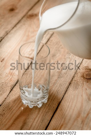 Milk from a jug pouring into glass on old wooden table - stock photo