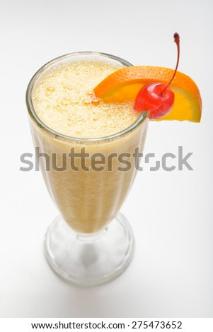 milk-fruit cocktail with cocktail cherry and orange slice - stock photo
