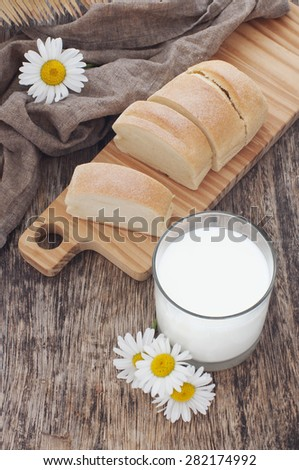 milk in a glass and fresh bread on a wooden table decorated with daisy - stock photo