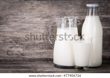 Milk in a group of jug, glass and bottle on dark wooden background.