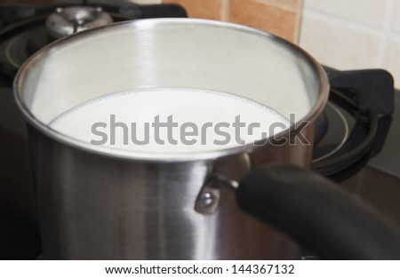 Milk in a saucepan on a gas stove burner - stock photo