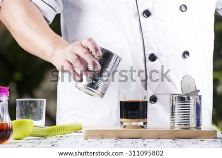 milk in can being poured into the cup of coffee - stock photo