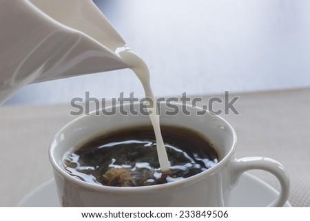 Milk in coffee - stock photo