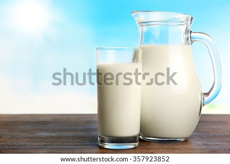 Milk in jar and in glass on table on blurred natural background