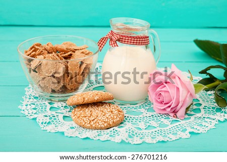 Milk in jug, cookies, muesli and rose with lace napkin on blue wooden background. Selective focus - stock photo