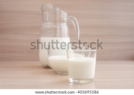 Milk in various glassware on a wooden background