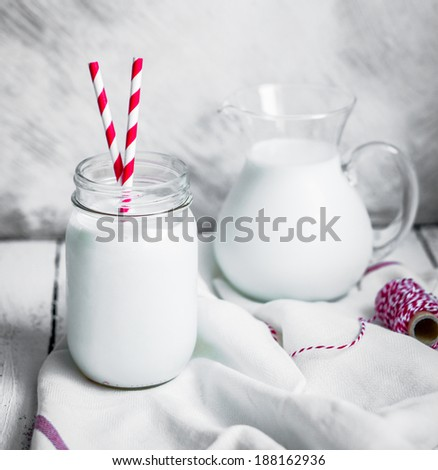 Milk jar on wooden rustic background - stock photo