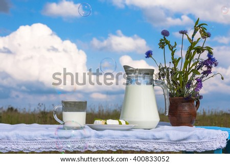 Milk jug and glass on wooden table. On a background of the summer sky with clouds. - stock photo