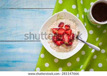 Milk oatmeal porridge with strawberries. Healthy Breakfast - stock photo