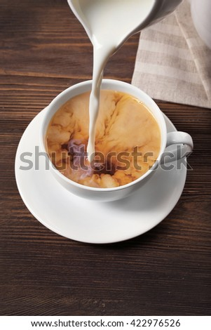 Milk poured into a cup of tea on wooden background. - stock photo