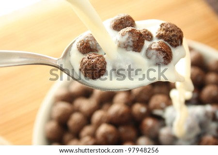 Milk pouring into bowl with chocolate balls. - stock photo