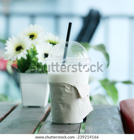 Milk shake  with a flower in coffee shop. - stock photo