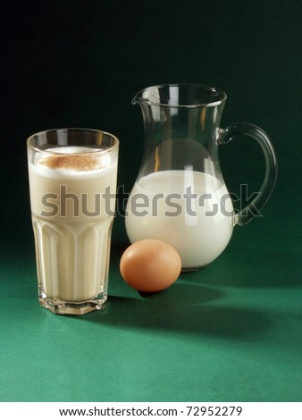milk shake with cacao, milk in pitcher and  egg on green  background