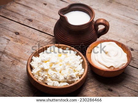 Milk, sour cream and curd on a wooden rustic board - stock photo