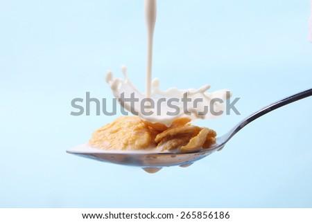 Milk splash on spoon of cornflakes - stock photo